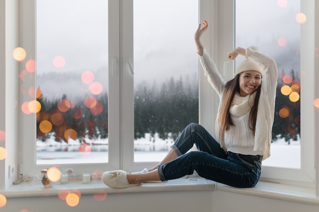 Smiling happy young attractive woman in stylish white knitted sweater, scarf and hat sitting at home on windowsill at christmas having fun holding hands up, winter forest background view, lights bokeh