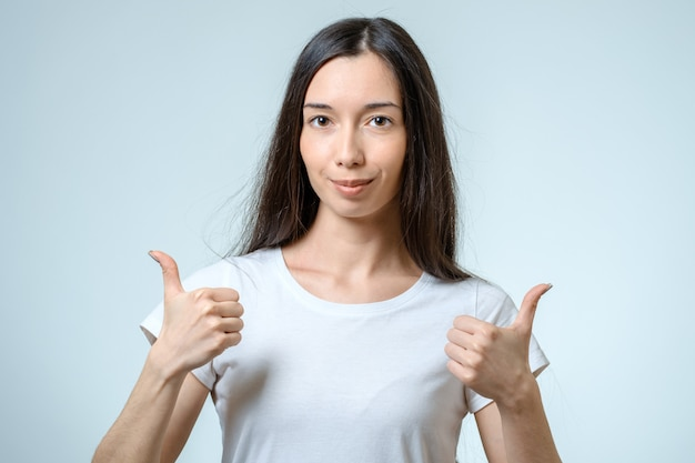 Smiling happy young brunette woman showing thumbs up gesture