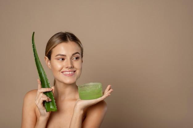 Smiling happy young female model holding aloe leaf and jar of aloe gel on beige