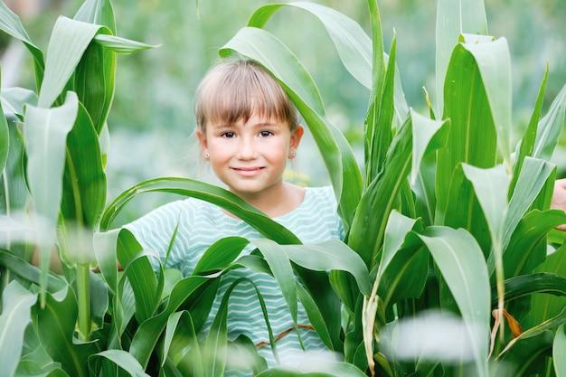 幸せな少女と緑の植物の葉の笑顔。晴れた暖かい日に農場に立っている美しいかわいい小さな女性。魅力的な人と背の高い栽培文化有機自然製品