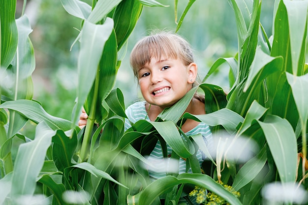 Smiling happy young girl and green plant leaves