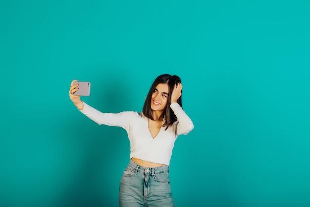 カジュアルな服、白いブラウス、青い表面で隔離のスマートフォンで自分撮りをしているジーンズを着て笑顔の幸せな少女。