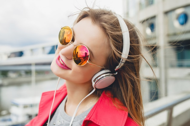 Smiling happy young hipster woman in pink coat listening to music on headphones, wearing sunglasses