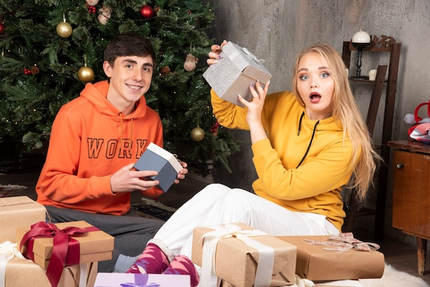 Smiling happy young married couple sitting near christmas tree with presents.