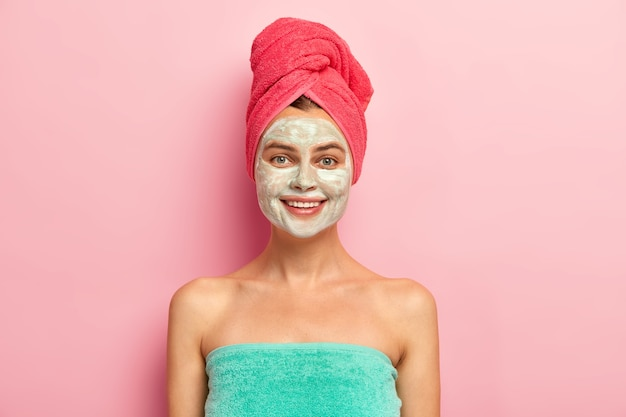 Smiling happy young woman applies nourishing homemade clay mask on face, pampers skin, wrapped in soft towel, cares about complexion, has natural beauty, models indoor
