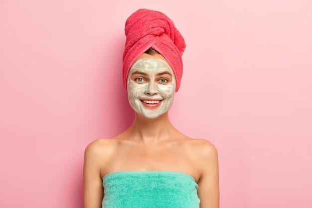 Sorridente giovane donna felice applica nutriente maschera all'argilla fatta in casa sul viso, coccola la pelle, avvolto in un asciugamano morbido, si preoccupa della carnagione, ha una bellezza naturale, modelli al coperto