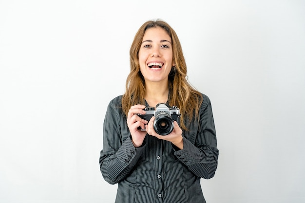 Smiling happy young woman holding an old vintage camera on white background