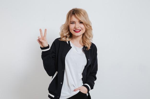 평화 제스처를 보여주는 캐주얼 옷에 웃는 행복 한 젊은 여자