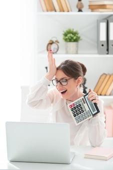 Улыбается счастливая молодая женщина в очках с калькулятором в офисе. удачный баланс.