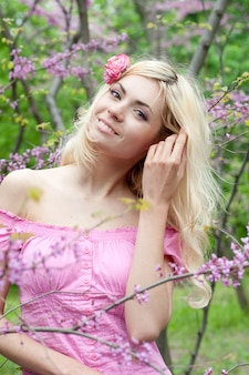 Smiling happy young woman portrait in spring park near blossom tree, healthy lifestyle concept