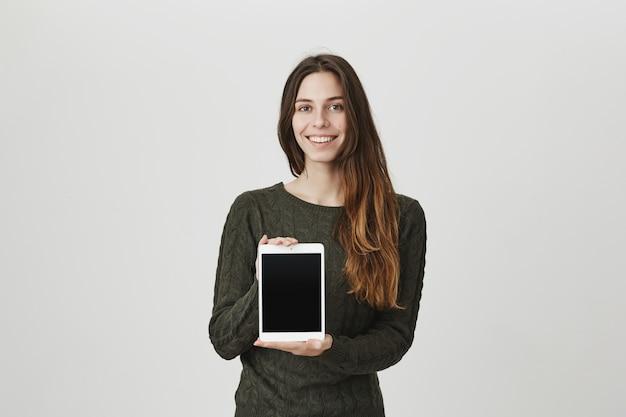デジタルタブレットの画面を見せて幸せな若い女の笑顔、アプリやショップを宣伝