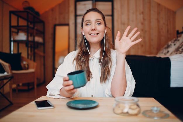 自宅のテーブルに座ってコンピューターのラップトップの後ろに座り、ビデオ通話の女の子の女性でお茶やコーヒーを飲みながら、室内のウェブカメラでオンラインで話す笑顔の幸せな若い女性