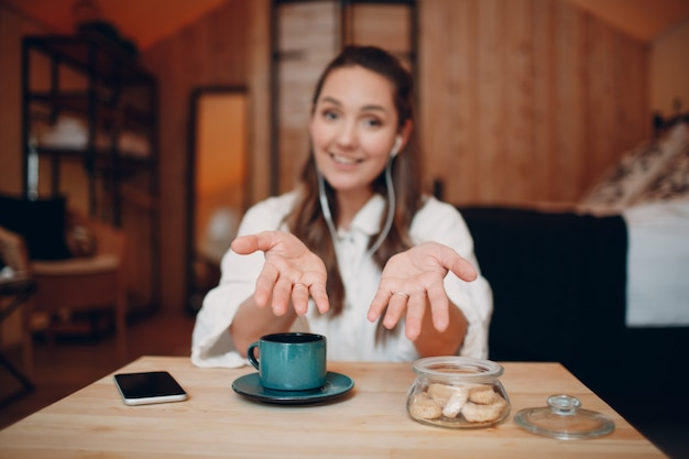웃고 있는 행복한 젊은 여성은 집에서 컴퓨터 노트북 뒤에 앉아 화상 통화를 하고 있습니다. 차 또는 커피 한 잔을 들고 실내 웹캠에서 온라인으로 말하는 여자 여자.