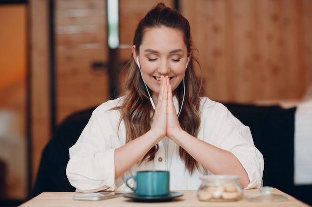 自宅のテーブルに座り、ビデオ通話で話している笑顔の幸せな若い女性、感謝の気持ちを持った女性の手で、室内のウェブカメラでオンラインで話す