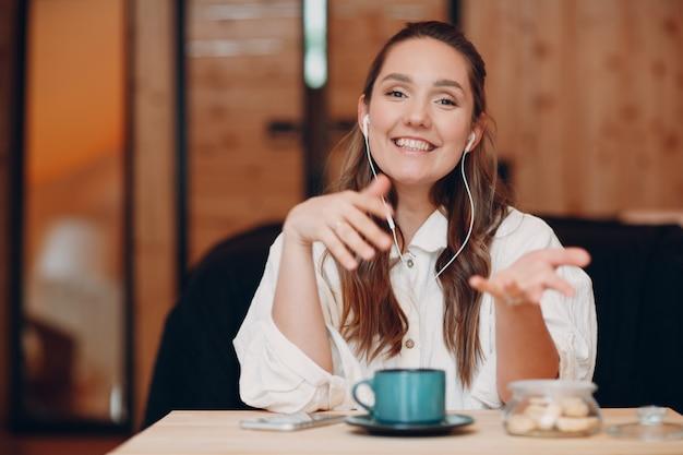 웃고 있는 행복한 젊은 여성이 집에서 컴퓨터 노트북 뒤에 앉아 화상 통화를 하고 있습니다...