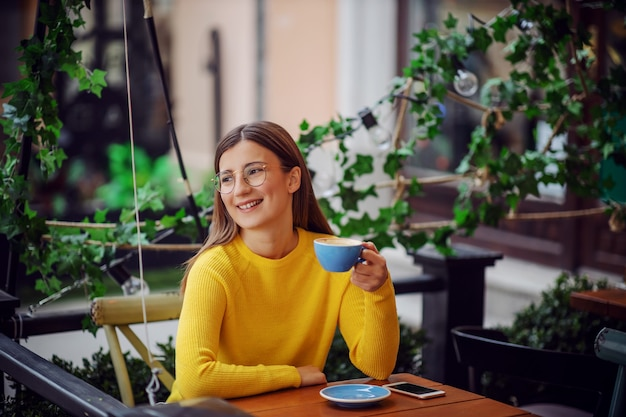 Smiling happy young woman sitting on terrace of cafe, holding cup of coffee and looking away.