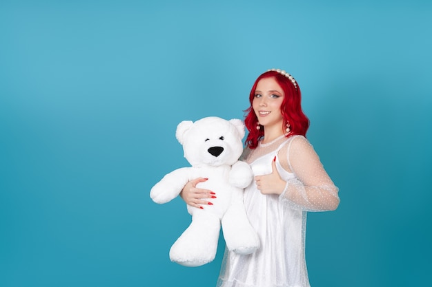 Smiling happy young woman in white dress with red hair holds white teddy bear and gives thumbs up