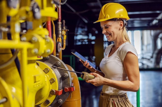 Улыбающаяся трудолюбивая женщина-руководитель в рабочей форме со шлемом на голове, стоя, держа планшет и проверяя тепло на трубе, стоя на теплоцентрали. женщина делает мужскую работу концепции.