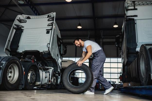 Улыбающийся трудолюбивый механик катит шину, чтобы поменять ее на грузовике. он находится в гараже импортно-экспортной фирмы.
