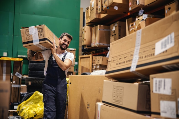 Smiling hardworking tattooed bearded blue collar worker in overalls carrying box on his shoulder and preparing it for export while walking trough warehouse.