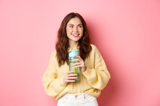 건강하고 스포티 한 갈색 머리 소녀 미소, 로고 옆으로 사려 깊은 찾고, 레몬 음료와 물병을 들고, 분홍색 벽에 서.