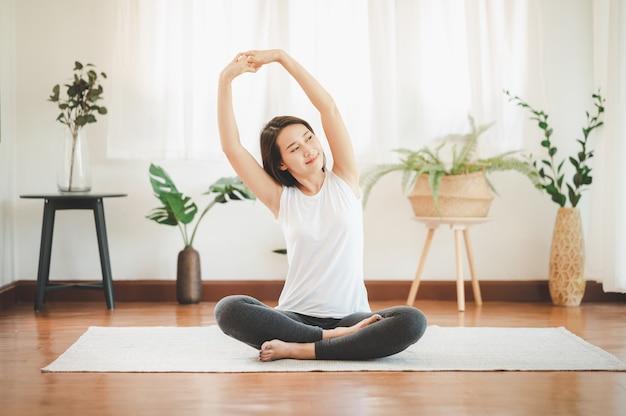 自宅でヨガの肩のストレッチをしている健康なアジアの女性の笑顔