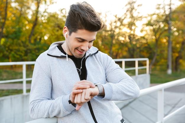 手すりで屋外に立って、スマートウォッチを見て健康なスポーツマンの笑顔