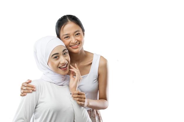 笑顔のヒジャーブの女の子と笑顔でカメラを見ているアジアの女の子