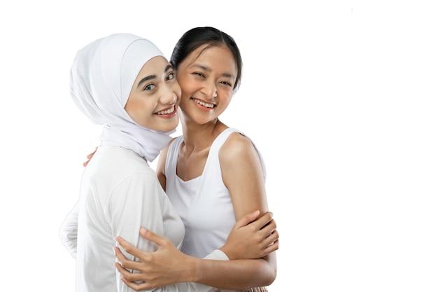コピースペースでカメラの前で笑顔のヒジャーブの女の子とアジアの若い女の子の親友