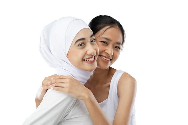 カメラの前で笑顔のヒジャーブの女の子と若い女の子の親友
