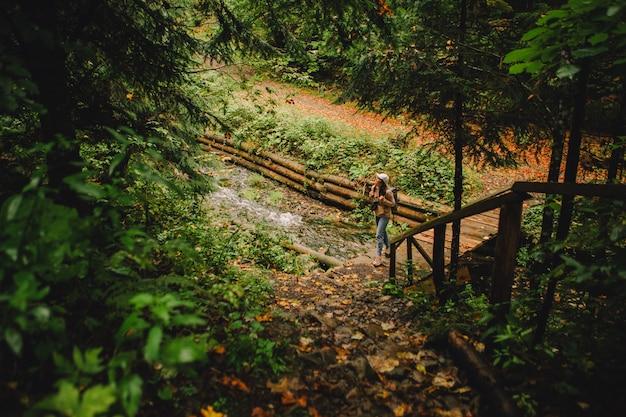 Улыбающаяся туристка женщина гуляет по осеннему лесу с копией пространства