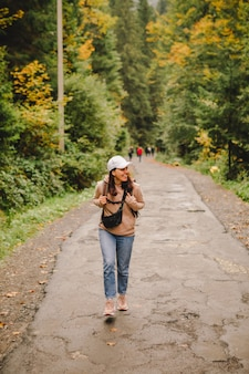 Smiling hiker woman walking by autumn forest road copy space