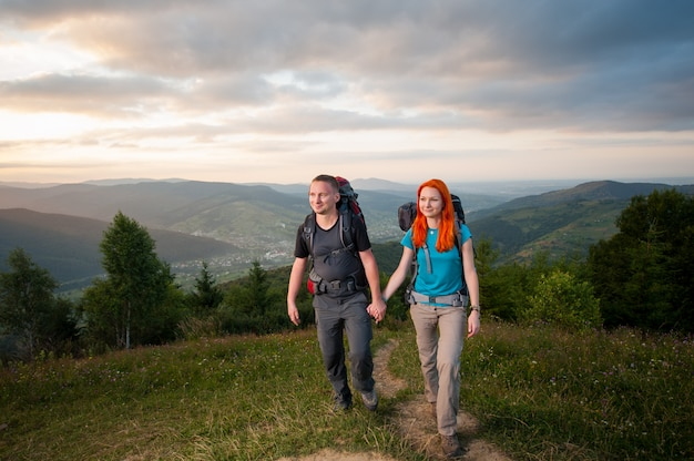 Smiling hikers man and woman with backpacks walking in the beautiful mountains area holding hands.