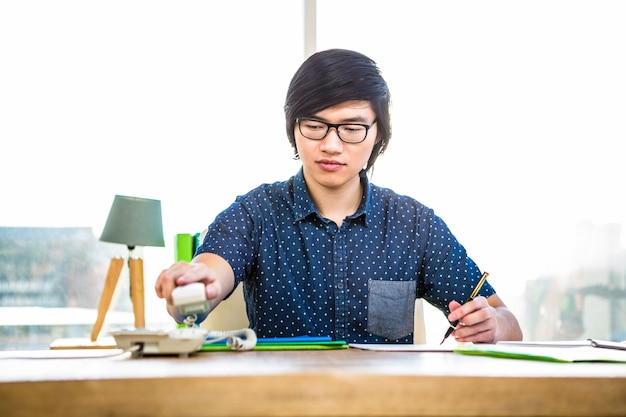 Smiling hipster businessman writing in office