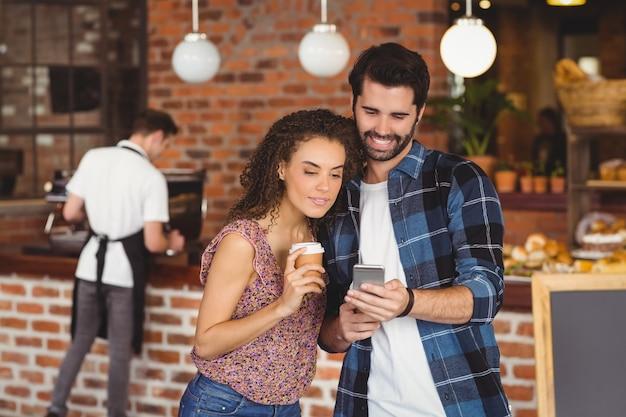 スマートフォンを見て笑いhipsterカップル