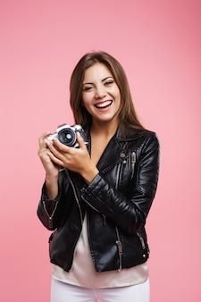 カジュアルな服装で笑顔の流行に敏感な女性は古いカメラを保持します。
