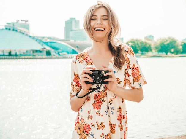 レトロなカメラを保持しているトレンディな夏のサンドレスで内気な少女の笑顔