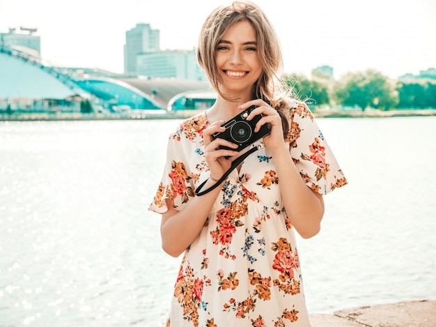 Smiling hipster girl in trendy summer sundress holding retro camera