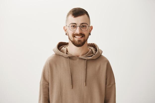 Улыбающийся хипстерский парень в очках и толстовке с капюшоном выглядит счастливым
