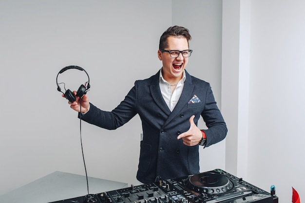 Smiling hipster guy with headphones at dj equipment