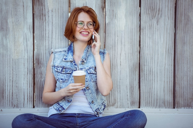 Smiling hipster holding a coffee cup, and on the phone