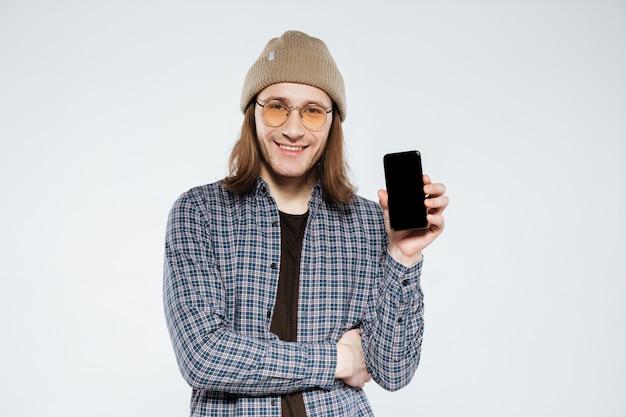 空白のスマートフォンの画面を示す眼鏡の流行に敏感な笑顔