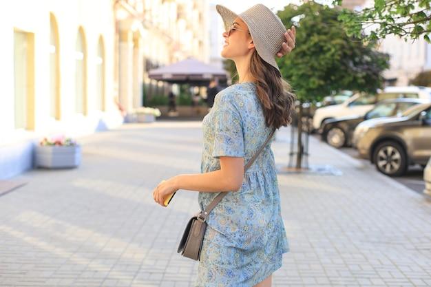 Улыбающаяся хипстерская модная девушка позирует на улице летом города, держа шляпу.