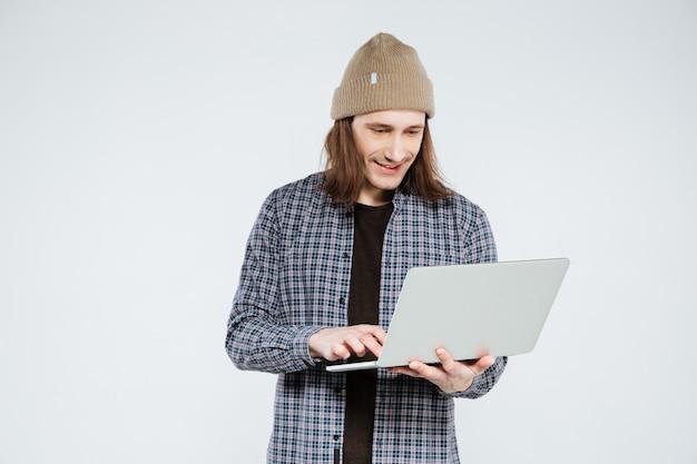 Smiling hipster using laptop
