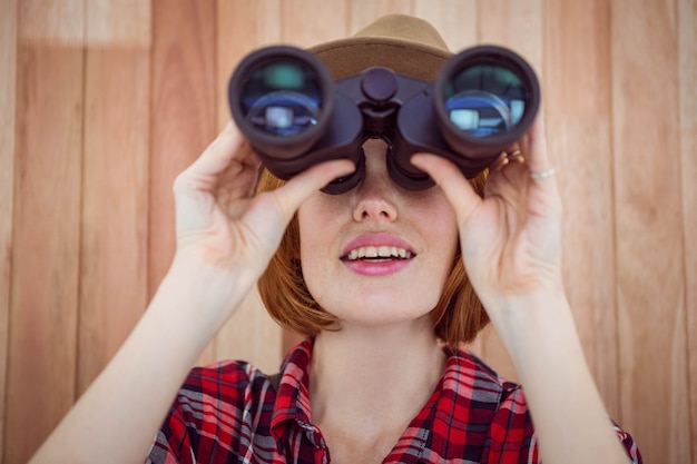 Smiling hipster woman looking through binoculars