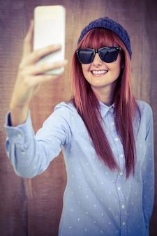 Smiling hipster woman taking selfie
