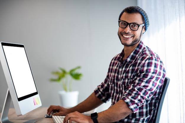 Smiling hipster working at computer desk
