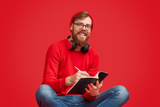 Smiling hipster writing in notebook