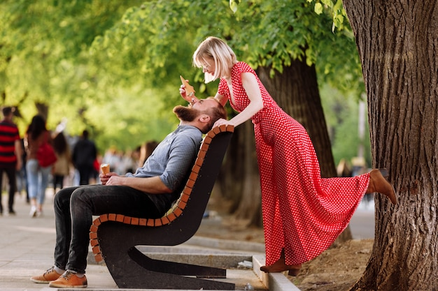 Smiling hipsters couple having fun and eating ice cream in the city. stylish young man with beard is sitting on a wooden bench and blonde woman in red dress woman fools around and plays with him