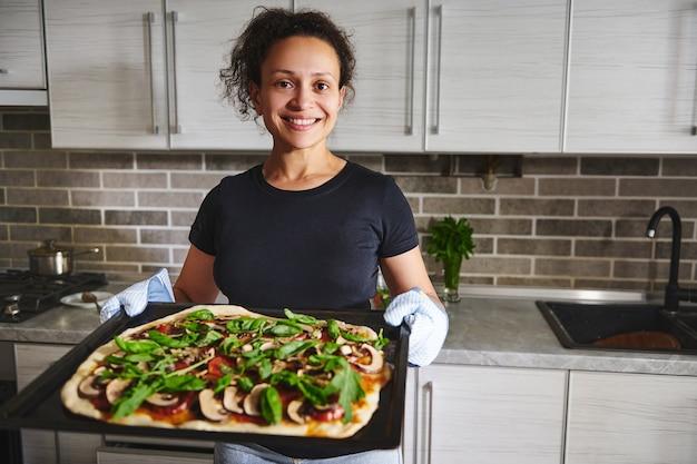 家庭の台所の背景に立って、オーブンからの熱いピザとベーキングシートを保持しているキッチンミトンで笑顔のヒスパニック系女性